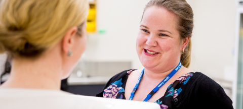 An over the shoulder photo of a woman wearing a Mercy Health lanyard smiling at another woman.