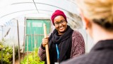 An over the shoulder photo of a female Mercy Health worker in a green house holding a gardening tool and smiling at a colleague